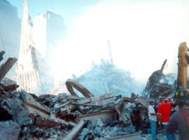 A small group of emergency personnel stands to the right of the massive pile of rubble at Ground Zero. Part of the South Tower still stands