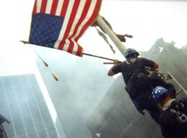 Two NYPD officers climb a ladder to raise an American flag near Ground Zero