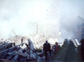 Firefighters in uniform traverse the rubble while others look on.