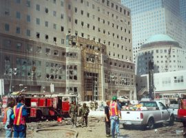 Emergency personnel and emergency vehicles line the muddy street in front of another building that was heavily damaged in the 9/11 attack