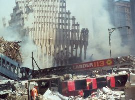 A destroyed firetruck rests in the rubble of the Twin Towers near the still-standing frame of the South Tower's base