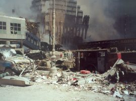 Thick black smoke rises from the frame of what was once the World Trade Center's South Tower. Destroyed vehicles, including a firetruck and an ambulance, lie in the rubble in the foreground