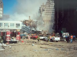 A street view near Ground Zero. Smoke rises from the still-standing skeletal building frame of the South Tower and piles of rubble; trucks, firefighters, and emergency vehicles fill the sludge-covered street
