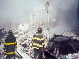 Two FDNY firefighters survey an immense pile of smoking debris