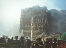 A crowd of firefighters stand in front of a heavily damaged building near the wreckage at Ground Zero. Still standing but crumbling, the building appears to be tilting backwards