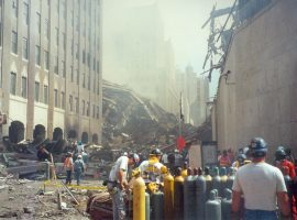 Emergency personnel in hard hats stand amongst large oxygen tanks, facing a collapsed building that has blocked the street.