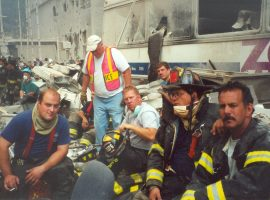 PWFD firefighters of Protection Fire Company take a rest near a destroyed MTA bus