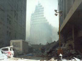 The skeletal frame of the South Tower is silhouetted through a haze of smoke, while destroyed vehicles and rubble line the street in the foreground.
