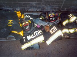 PWFD firefighters' helmets, jackets, and personal belongings displaying names and numbers piled on the ground