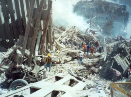 Emergency personnel stand atop a smoking pile of rubble at Ground Zero. A wheel from the landing gear of one of the planes to hit the Towers can be seen in the wreckage in the left foreground.