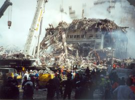 Emergency personnel stand amongst cranes and other construction vehicles at Ground Zero