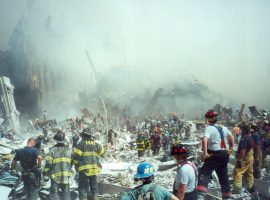 A large crowd of firefighters and emergency personnel stand atop the smoking debris of the World Trade Center