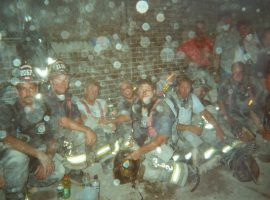 Firefighters in uniform, including members of PWFD's Protection and Atlantic companies, seated in front of a brick wall at night - partially obscured by dust particles from the World Trade Center that fill the air and reflect light from the camera flash
