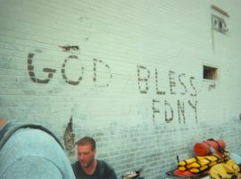 """Emergency responders rest by a white brick wall bearing the legend """"GOD BLESS FDNY."""""""