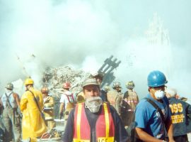 Firefighters and police in protective gear stand amongst the smoking rubble of the South Tower.